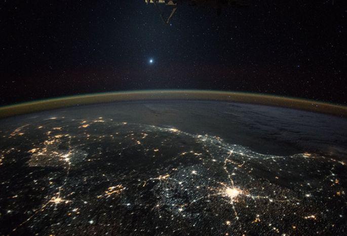 Венеры из космоса на фоне ночных огней Земли